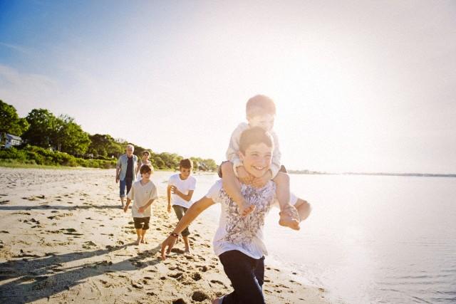 Boys (4-9) running along beach